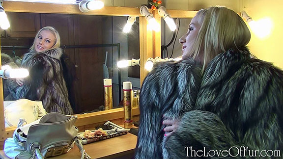 Danielle Maye looks at herself in silver fox fur in the mirror