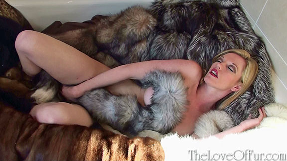 Holly Kiss relaxes in a bath full of fur coats and stoles